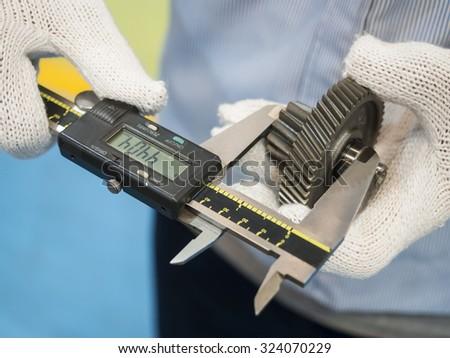 Operator inspection automotive steel gear by vernier caliper - stock photo