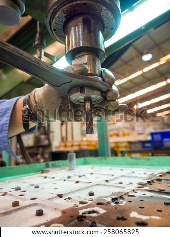 operator machining mold and die parts for automotive by radius drilling machine - stock photo