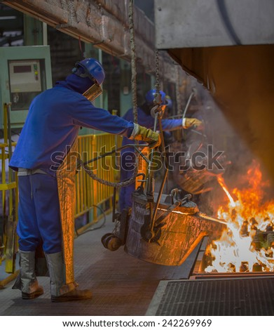 operator pouring automotive part in casting line - stock photo