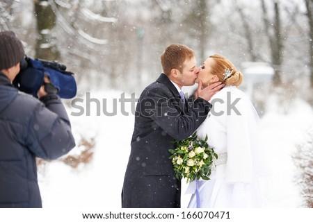 Operator shooting romantic kiss happy bride and groom on winter wedding day - stock photo
