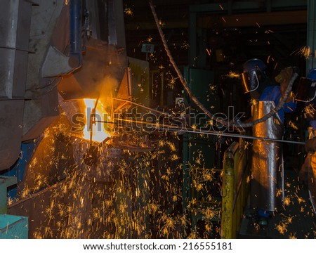 operator tapping molten metal in iron casting factory - stock photo