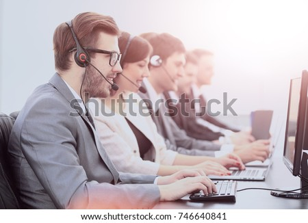 operators with headsets in front of computers in the call center