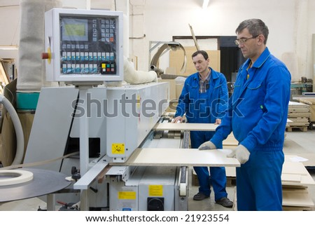Operators working with wood paneling machine