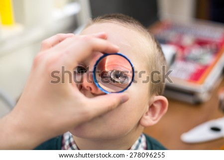 ophthalmologist examines the eyes of a boy through a magnifying glass - stock photo