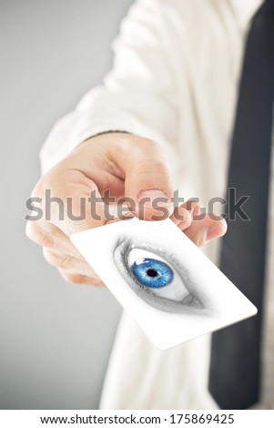Ophthalmologist giving his visiting card, selective focus on fingers and card - stock photo