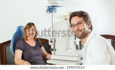 Ophthalmologist In Exam Room With Mature Woman - stock photo