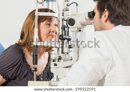 Ophthalmologist In Exam Room With Mature Woman Sitting In Chair Looking Into Eye Test Machine - stock photo
