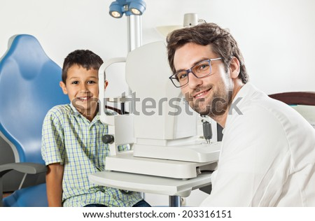 Ophthalmologist In Exam Room With Young Boy