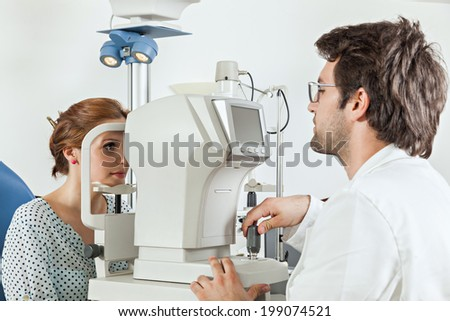 Ophthalmologist In Exam Room With Young Woman Sitting In Chair Looking Into Eye Test Machine - stock photo