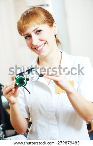 Ophthalmology. portrait of female optometrist optician doctor with test glasses phoropter in eye correction medic clinic  - stock photo