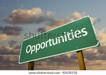 Opportunities Green Road Sign with dramatic blue sky and clouds. - stock photo