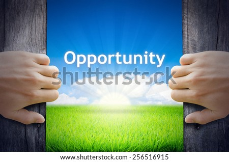 Opportunity. Hand opening an old wooden door and found Opportunity word floating over green field and bright blue Sky Sunrise. - stock photo