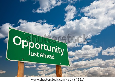 Opportunity, Just Ahead Green Road Sign with Copy Room Over The Dramatic Clouds and Sky. - stock photo