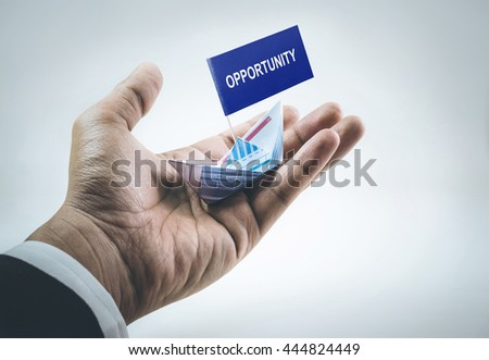 Opportunity word on flag with boat made of paper graph in businessman hand.For business financial concept.