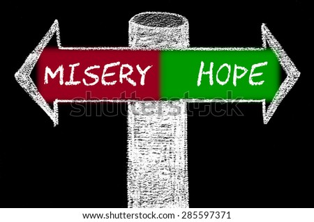 Opposite arrows with Misery versus Hope.Hand drawing with chalk on blackboard. Choice conceptual image - stock photo
