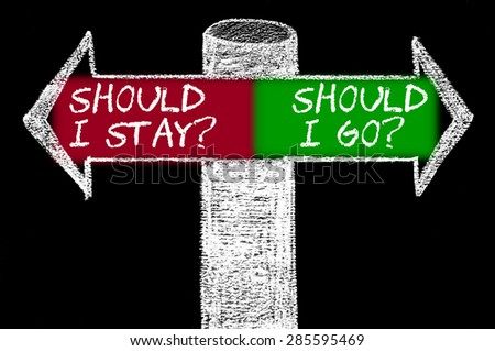 Opposite arrows with Should I Stay versus Should I Go.Hand drawing with chalk on blackboard. Choice conceptual image - stock photo