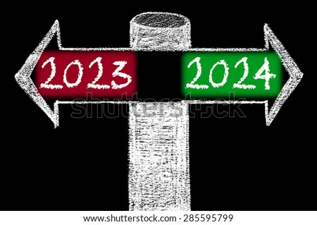 Opposite arrows with Year 2023 versus Year 2024.Hand drawing with chalk on blackboard. Choice conceptual image - stock photo