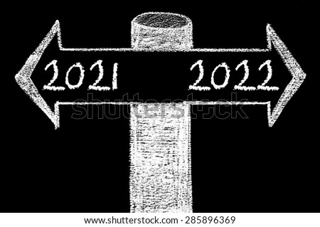 Opposite arrows with Year 2021 versus Year 2022.Hand drawing with chalk on blackboard. Choice conceptual image - stock photo
