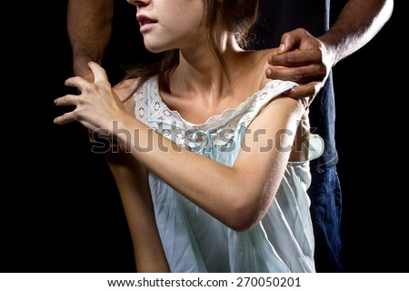 Oppressive man behind a female victim of domestic violence or abuse.  Woman is resisting or fighting back by pushing his hands away. - stock photo