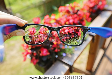 optical eyeglasses in the hand over blurred flower background - stock photo