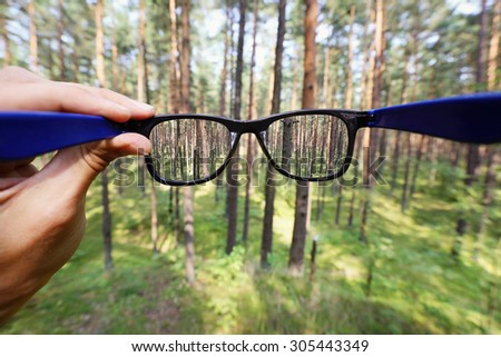 optical eyeglasses in the hand over blurred forest background - stock photo