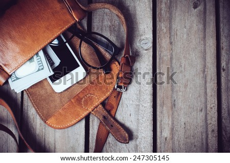 Optical glasses, money and smartphone in an open leather hipster's bag on a wooden board background. - stock photo