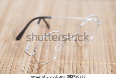 Optical round glasses on wooden background