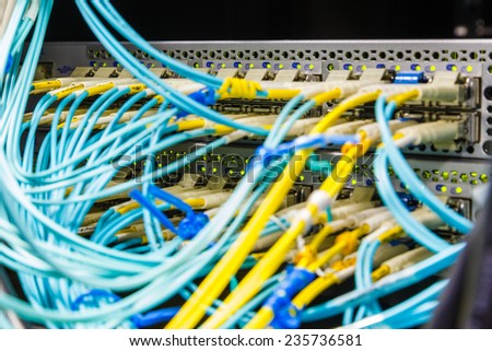 Optical switch and colorfull FC cables connected equipment in data center - stock photo