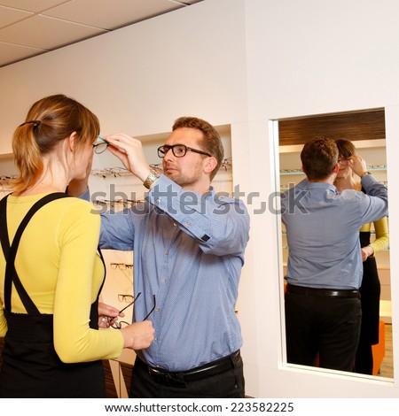 Optician checks glasses in a shop - stock photo