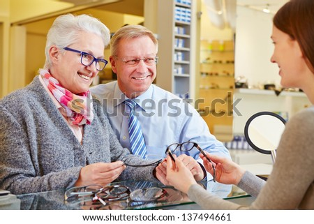 Optician consulting senior couple for buying new glasses - stock photo