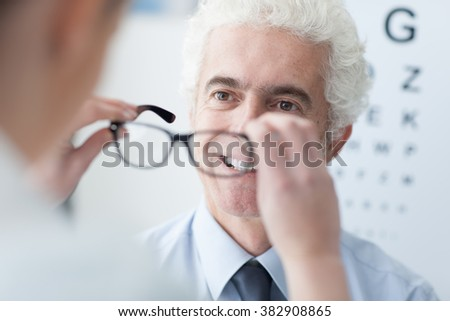 Optician giving new glasses to a male patient, he is smiling, eye chart on the background - stock photo