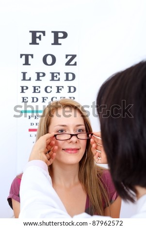 Optician helps woman to choose the best pair of glasses - stock photo