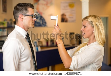 Optician or optometrist measuring the eye distance of a customer with a tablet computer - stock photo