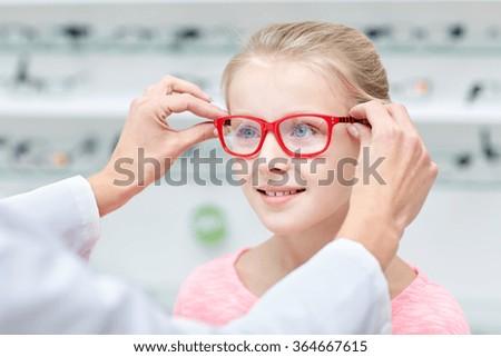 optician putting glasses to girl at optics store - stock photo