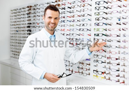 Optician selling glasses. Eye doctor, optometris at work. - stock photo