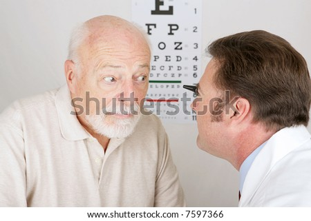 Optician using and ophthalmoscope to look into a patient's eyes. - stock photo