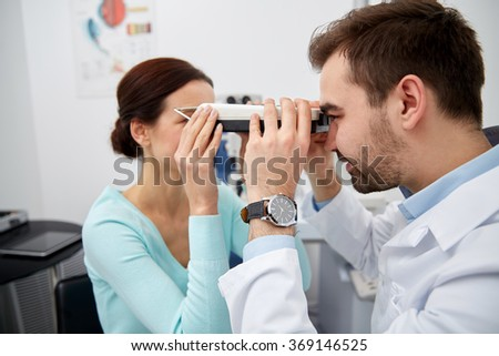 optician with pupilometer and patient at eye clinic - stock photo