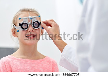 optician with trial frame and girl at clinic - stock photo