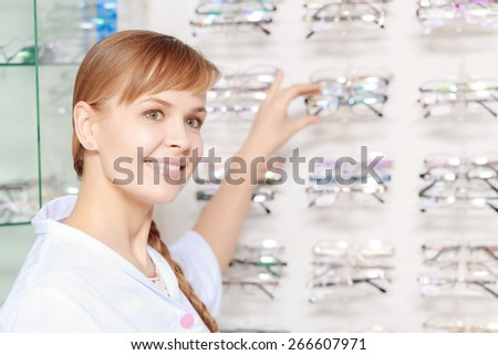 Optics. Close-up of a young beautiful female pharmacist picking up the glasses from the stand in a drugstore - stock photo