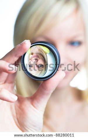 Optics concept: pretty young woman showing the principle of imaging through a lens (focus on the image through lens) - stock photo