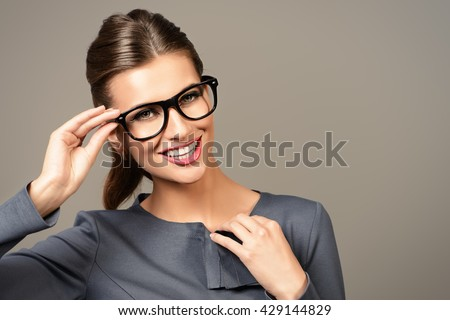 Optics style. Portrait of a beautiful smiling young woman wearing elegant glasses. Beauty, fashion. Cosmetics, make-up. Business style. - stock photo