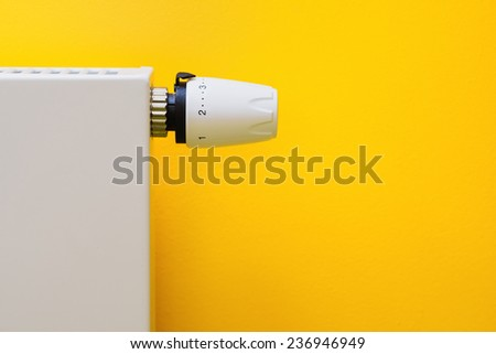 Optimal setting of the thermostat valve - yellow background. Save energy and money concept - stock photo