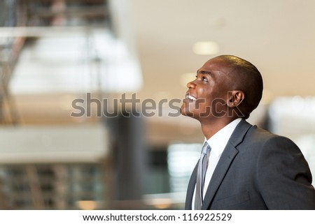 optimistic african american businessman looking up