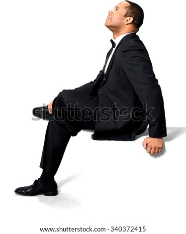 Optimistic African man with short black hair in evening outfit with hands holding leg - Isolated