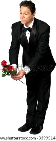 Optimistic Caucasian man with short black hair in a tuxedo holding red roses - Isolated