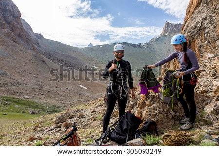 Optimistic climber. Two people on rocky terrain man doing OK sign smiling optimistic face female packing her backpack preparing for ascend mountain landscape rising sun background warm tone red rocks