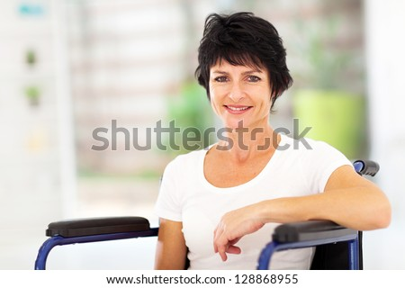 optimistic handicapped middle aged woman sitting on wheelchair - stock photo