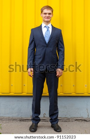 Optimistic Young man standing against yellow wall - stock photo