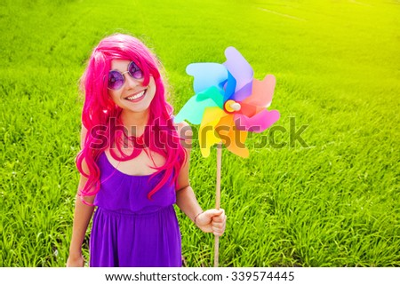 optimistic young woman wearing pink wig posing outdoors with windmill - stock photo