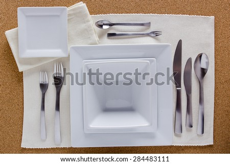 Option table setting with square plates and a complete set of forks, knives and spoons. - stock photo